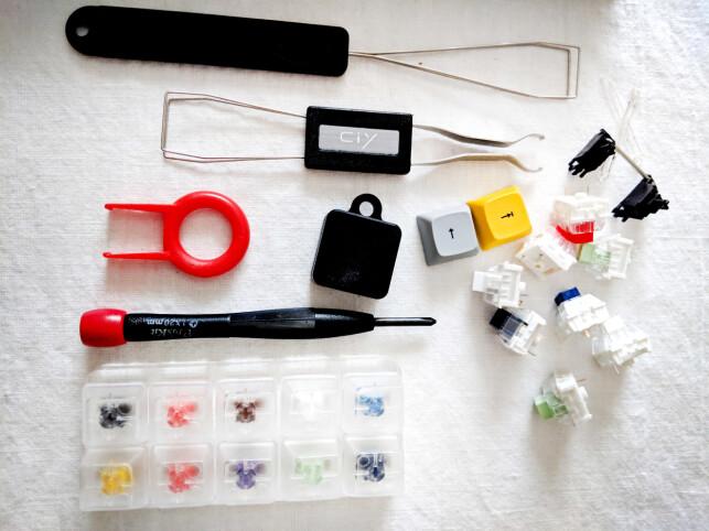 """Diverse verktøy og deler Eivind B. Smedseng bruker for å bygge tastaturene sine. Øverst ser du verktøy for å fjerne keycaps og brytere, til høyre noen brytere og stabilisatorer, nederst et rigg for å teste brytere i forskjellige """"farger"""", som avgjør hvordan de kjennes og høres ut. 📸: Eivind B. Smedseng"""