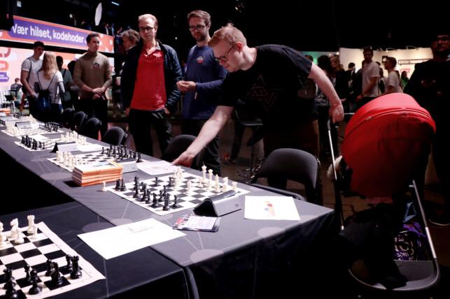 Sopra Steria sin stand på JavaZone 2019. De satsa alle penga på at utviklere liker sjakk. Jørgen pirker litt borti bordet og later som han vet hva han driver med. 📸: Ole Petter Baugerød Stokke