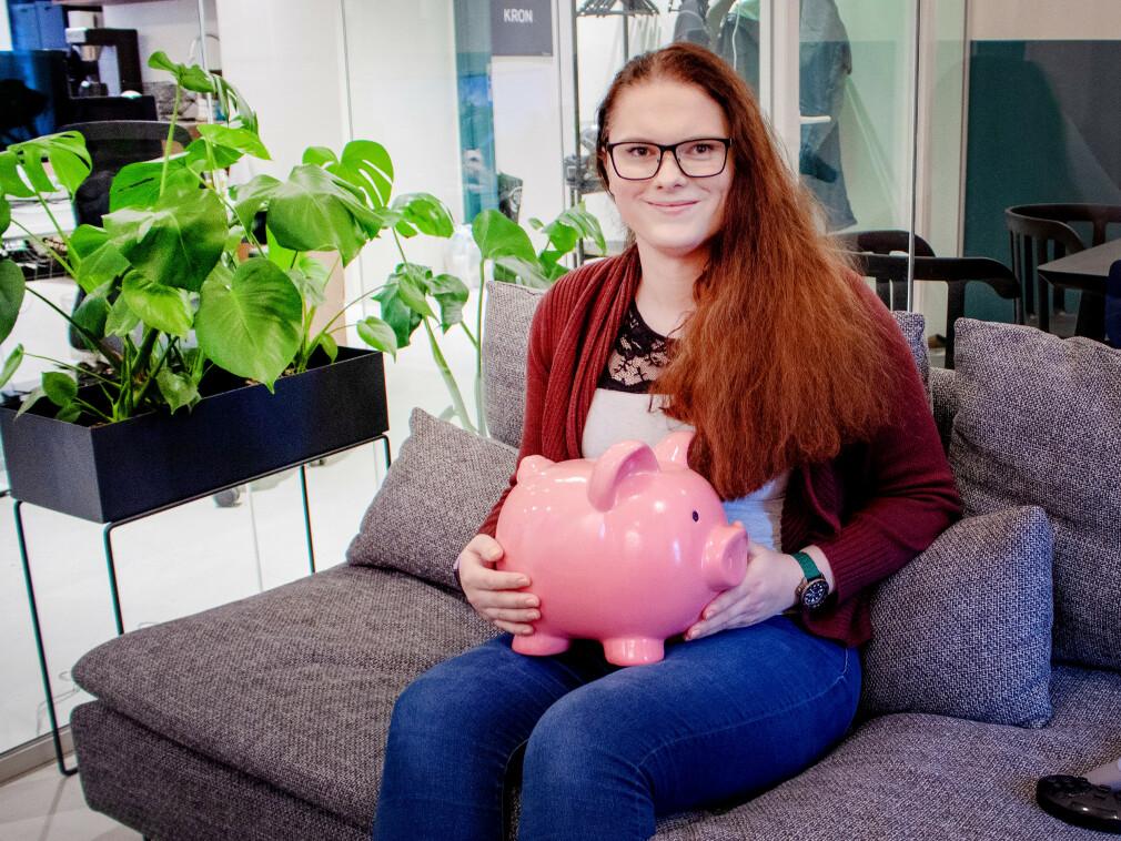 Benedicte Emilie Brækken sammen med en sparegris. Hun er tross alt CTO i Kron; en app som skal gjøre det enklere å spare i fond. 📸: Privat
