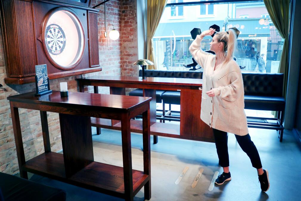 Salgs- og booking-ansvarlig Lovisa Hillberg på Oche tar seg et slag dart. Strekene du ser på gulvet foran beina hennes er opphavet til navnet; for ja, de heter oche, eller kastelinje. 📸: Ole Petter Baugerød Stokke