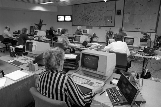 """""""Innføring av data går ikke like smertefritt på alle arbeidsplasser. Her interiør fra Oslo Taxisentral, der man etter et styremøte har vedtatt å gå inn for fortsatt drift av sitt kostbare datautstyr, til tross for problemer med utstyret. Oversiktsbilde av stort rom med menn og kvinner i arbeid ved dataskjermer / datamaskiner / computere."""" 📸: Henrik Laurvik / NTB Scanpix"""