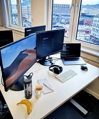 """""""Jeg har rydda pulten for anledningen, men det er egentlig slik jeg liker å ha det (selv om det sklir fort ut igjen). Og jeg er veldig fornøyd med utsikten"""" forteller Dfind-utvikleren Kristoffer Rene Eckhoff, her hos Ruter. 📸: Privat"""