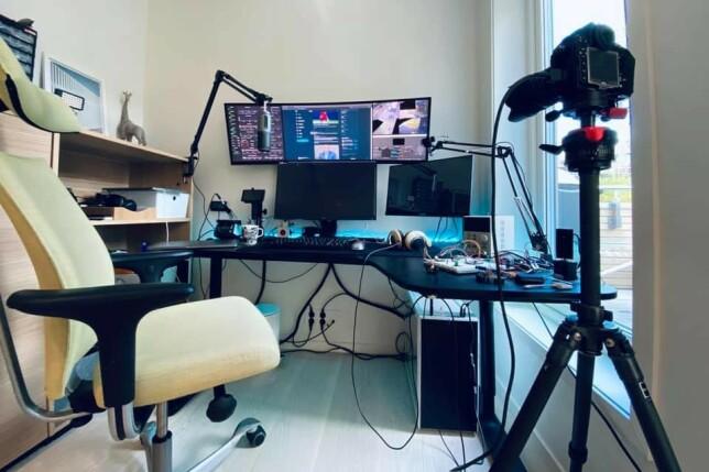 """""""Mye er som før. Jeg har feks ikke ryddet i ledningene mine enda.  Fikk etter hvert skaffet webcam og mikrofon, førstnevnte montert på stativet til en Ikea-bordlampe, med 3d-printet adapter til minikulehode - så jeg kan vri det rundt og vise kretskort og annet jeg jobber med. Har også kjøpt en Camlink 4k, dvs hdmi-til-usb3, så jeg kan bruke speilrefleks som sekundært webcam, eller ha live-view fra mobilen. Mao. godt rigget for streaming - noe jeg aldri gjør 🤷🏼Bredskjermen, kjøpt i starten av koronatid, er stort sett dedikert til Grafana-dashboard for servere rundt omkring i og utenfor huset, og feed fra noen kameraer, men har i økende grad også fått bidra som avlastningsskjerm ved utvikling. Sideskjermen, som dreper nakken, bruker jeg mest til meldinger og denslags. I blant får den være ui for usb-basert oscilloskop, og det tror jeg den liker aller best."""" 📸: Einar Otto Stangvik"""