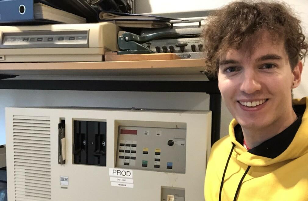 Utvikler Eirik Sletteberg i NAV poserer foran hardware som ble brukt til å kjøre Det Sentral Folketrygdsystemet i produksjon. Bildet er tatt på NAV sitt teknologi-museum. 📸: Privat