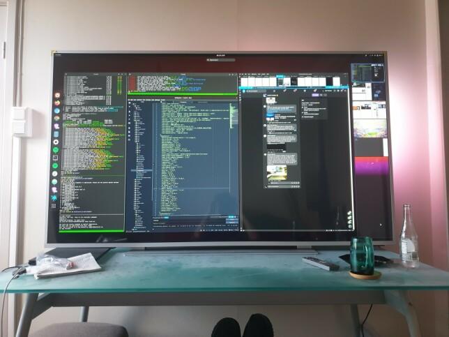 """Just Thomas Hiorth Misund: """"Størrelsen teller. 75 tommer, 4k. Shelltile i Gnome. Bluetooth-mus og tastatur. Med denne oppsettet kan jeg variere arbeidsstilling mellom kontorstol helt nærme og sofa litt lengre unna. En god tiling-løsning er viktig for å kunne sortere en skjerm på denne størrelsen - det er ikke like nærliggende å gå i fullskjerm på et enkelt vindu som det er på mindre skjermer."""""""