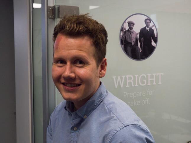 VP produktutvikling Julian Veisdal hos Disruptive Technology foran en av kontordørene hos DT som hadde avbildet de kjente fly-pionerene Wright-brødrene. 📸: Isak Løve Pilskog Loe