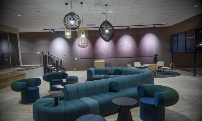 SpareBank 1 har gått bort fra rødt og blått, og heller valgt lune norskinspirerte farger og materialer. Møblene er mye gjenbruk, som stoler, bord og alle gulvene er avkapp i treproduksjon. 📸: Robert S. Eik.